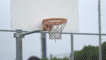 A young man shooting hoops on an outdoor basketball court. video