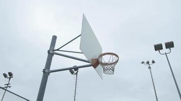 um jovem jogador de basquete mergulhando em uma quadra de basquete ao ar livre. video