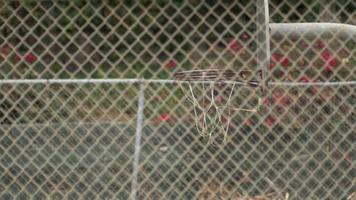 A young man basketball player dunking on an old outdoor basketball hoop. video