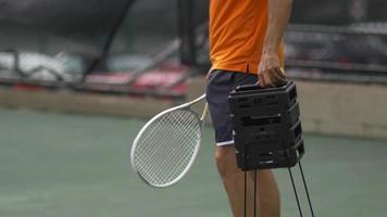 jugador de tenis masculino recolectando pelotas de tenis con raqueta. video
