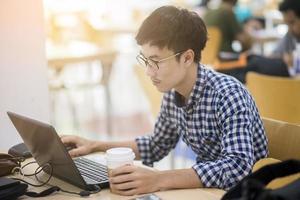 Estudiante universitario trabaja con su computadora portátil en la biblioteca foto