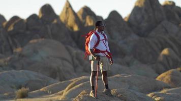 portrait d'un jeune homme faisant de la randonnée sur des rochers dans un désert montagneux. video
