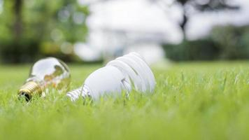 Lightbulb in green grass, save the earth concept photo