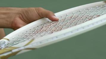 Man adjusting the strings on a tennis racket. video