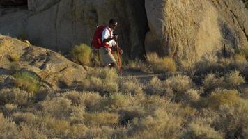 un jeune homme sac à dos sur des rochers dans un désert montagneux. video