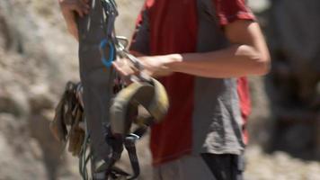 um jovem preparando sua corda antes de escalar. video