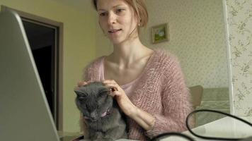 Attractive woman with kitten using laptop video