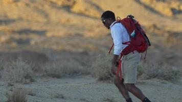 un jeune homme faisant de la randonnée dans un désert montagneux. video