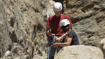 um jovem usando um nó de seguimento em forma de oito para amarrar sua corda ao arnês durante uma escalada. video