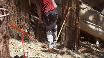 un homme en équilibre sur une slackline entre deux arbres dans le désert. video