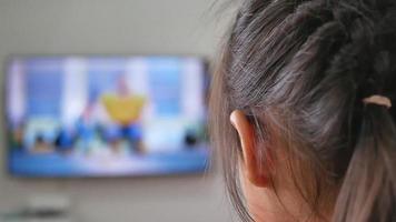 jolie petite fille regardant la télévision dans le salon, restez à la maison pendant l'épidémie de coronavirus. video
