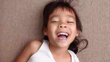 linda niña acostada en el sofá de la sala de estar, mirando a la cámara y sonriendo mientras juega en casa. video