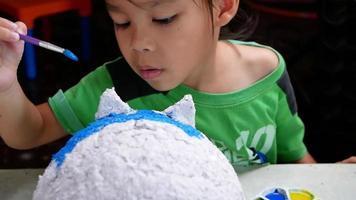 A little girl paints with a brush on the figure of a white pig-shaped papier-mache at home. Make your own piggy bank. video