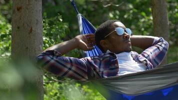 um homem descansando em uma rede perto de um lago na montanha. video