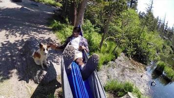 pov de un hombre descansando en una hamaca cerca de un lago de montaña con su perro. video