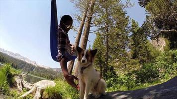 un hombre descansando en una hamaca con su perro cerca de un lago de montaña. video