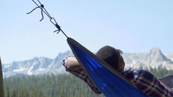 un hombre descansando en una hamaca cerca de un lago de montaña. video