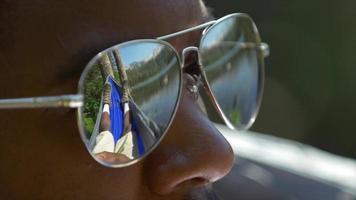 primer plano extremo del hombre con gafas de sol descansando en una hamaca cerca de un lago de montaña. video
