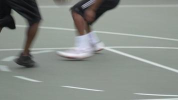 Two young men playing one on one basketball against one another. video