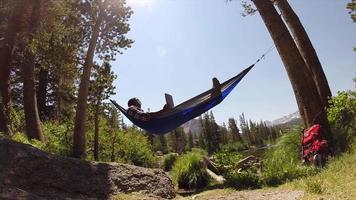un hombre descansando en una hamaca y usando un dispositivo móvil tableta cerca de un lago de montaña. video