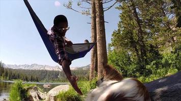 um homem descansando em uma rede com seu cachorro perto de um lago na montanha. video
