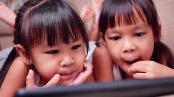 Two sibling girls lying on the sofa and watching digital tablets together in the living room. video