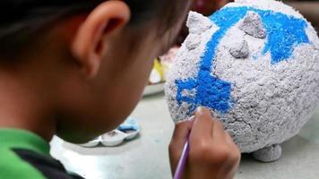 une petite fille peint avec un pinceau sur la figure d'un papier mâché blanc en forme de cochon à la maison. fabrique ta propre tirelire. video