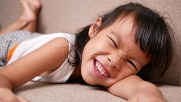 Cute little girl lying on sofa in the living room, looking at camera and smiling while playing at home. video