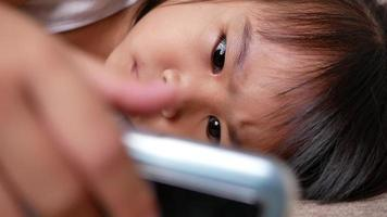 Cute little girl lying on the sofa and watching a smartphone in the living room. video