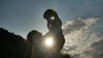 la silueta de la madre feliz sosteniendo a la niña sonriendo y jugando en el fondo del atardecer en el parque. video