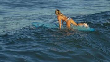 A young woman surfing in a bikini on a longboard surfboard. video