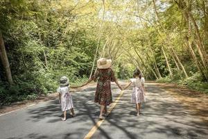 madre e hijas caminando en un parque foto