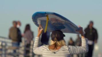 une jeune femme faisant de la planche à roulettes en longboard tout en équilibrant une planche de surf sur sa tête. video