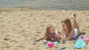 Mom and daughter on the river bank eat ice cream Outdoor recreation video