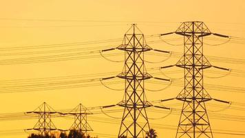 Towers support the high tension power lines at sunset. video