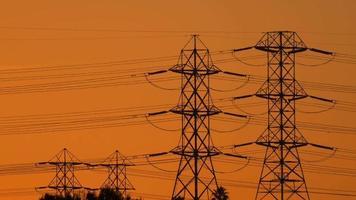 torres sustentam as linhas de alta tensão ao pôr do sol. video