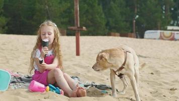 fille mange de la crème glacée et nourrit le chien à l'extérieur video