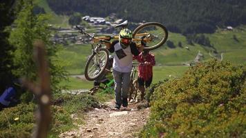 um grupo de ciclistas de montanha sobe a colina com suas bicicletas. video