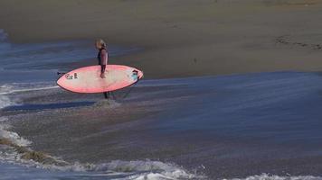 una mujer monta una tabla de paddle surf de pie mientras practica surf en una tabla de surf rosa. video