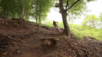 travelling d'un homme faisant du vélo de montagne dans une forêt. video
