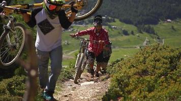 un groupe de vététistes gravit la colline avec leurs vélos. video