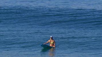 A young woman in a bikini sitting on her longboard surfboard. video