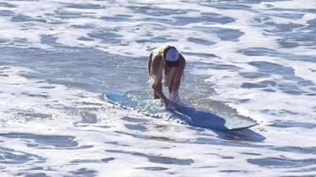 A young woman in a bikini walking with her longboard surfboard. video
