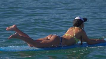 A young woman in a bikini paddling on a longboard surfboard. video