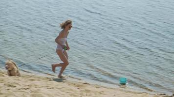 mamma och dotter springer längs flodstranden med en solig sommardag för hundsemester video