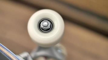 en ung man snurrar på hjulet på sin skateboard på ett torg. video