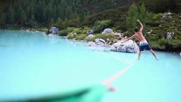 A man falls while slacklining on a tightrope and walking over a lake. video