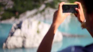 un hombre toma fotos de su amigo que se balancea en una cuerda floja y camina sobre un lago. video