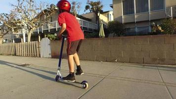 um menino anda de scooter em um bairro. video
