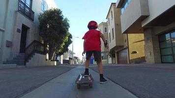 een jongen rijdt op een skateboard in een steegje in de buurt. video